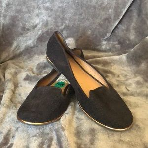 Report black flats with gold trim.